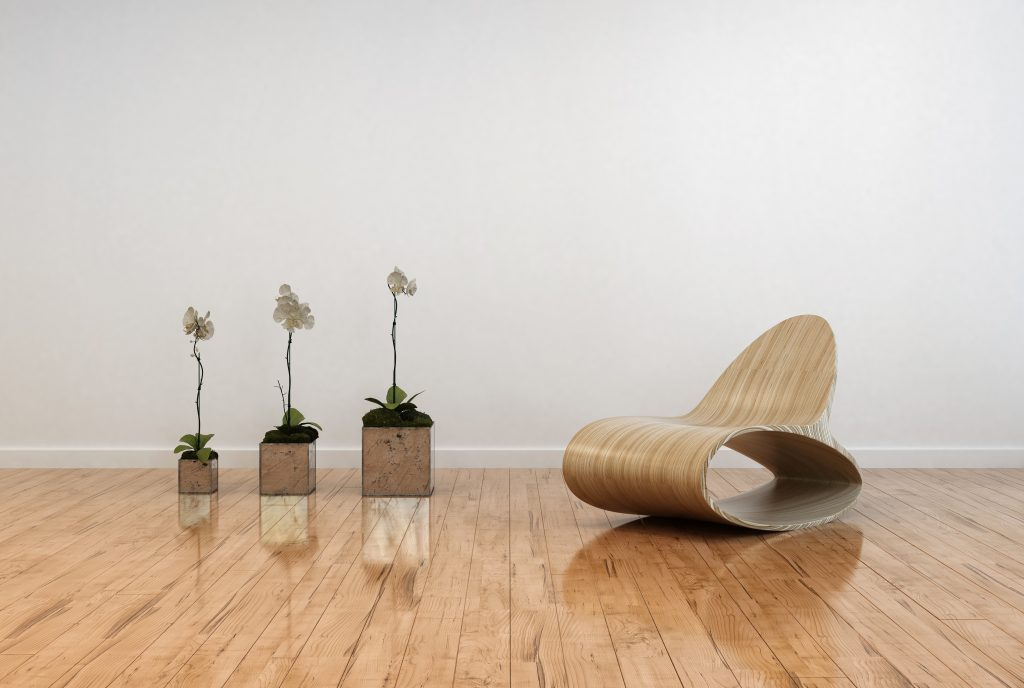 Stylish contemporary living room interior with an unusual bentwood chair facing three potted orchids in flower on a polished shiny parquet floor and white wall
